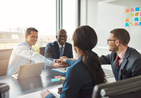 affirm: Successful multiracial business team working together affirm their commitment by linking hands across an office table during a meeting Stock Photo