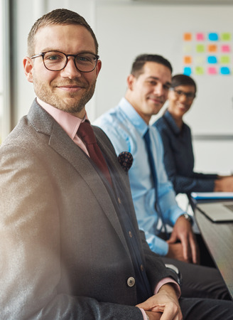 Handsome bearded man wearing suit and tie with two management colleagues in meeting at conference table in front of large white board