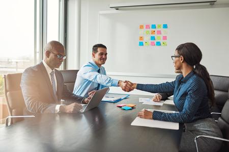 사무실에서 회의 테이블에서 다인종 비즈니스 회의 축하에 테이블을 가로 질러 손을 흔들면서 두 사업 동료