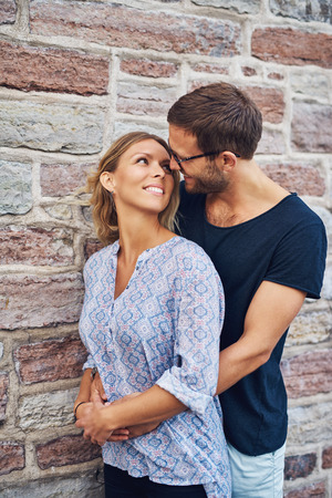 romantically: Half Body Shot of a Man Hugging his Woman from Behind Romantically and Smiling Each Other Against Brick Wall Background. Stock Photo