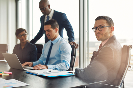 Professional young multiracial business team seated working around a table in the office with a young man in the foreground turning to look at the camera Stock Photo