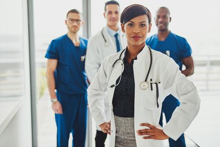 mujer médico negro a cargo en el hospital, lo que lleva equipo médico médicos y cirujanos om Foto de archivo