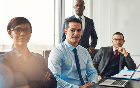 관리 결정을 내리는 사무실의 회의실에있는 테이블에 앉아 자신감을 가진 인종적 비즈니스 팀을 미소 짓는다. 스톡 콘텐츠