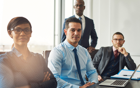managerial: Smiling confident multiracial business team seated at a table in a conference room in the office making managerial decisions