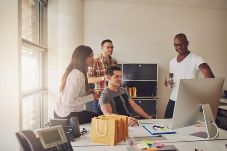 Vier jonge volwassenen zitten rond bureau met computer, telefoon, notities en pen en papier naast het lichte kantoorvenster Stockfoto