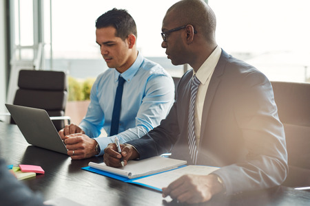 ejecutiva en oficina: Dos ejecutivos de negocios con experiencia en una reunión sentado en una mesa discutiendo el papeleo y la información en un ordenador portátil, un hispano, un afroamericano Foto de archivo