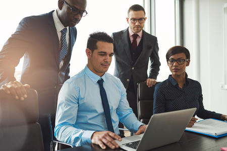 Group of diverse business people in formal clothing inside their office discussing or looking at information on a laptop computer