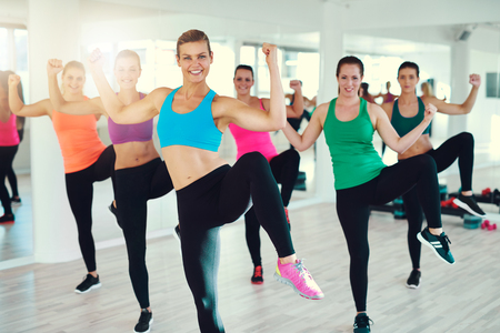 synchronously: Group of active young women doing exercise together and looking at camera