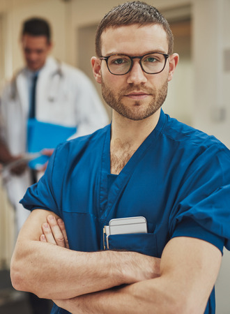 Serious confident young surgeon wearing glasses and surgical scrubs standing in a hospital with folded arms looking intently at the camera