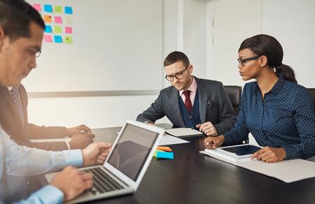 Fraktion der Rassen Geschäftskollegen in einer Sitzung an einem Tisch im Büro arbeiten auf Laptops und Papierkram sitzen