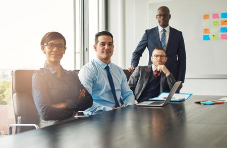 4 つの自信を持って成功した多民族の多様なビジネス パートナーや仲間会議テーブル会議を持ち、一時停止に座ってカメラに笑顔を
