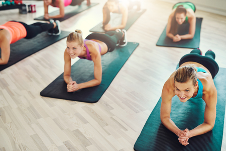 synchronously: Fit young women doing exercise on abs synchronously