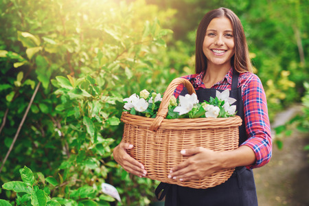 florist shop: Happy woman enjoying her work at the nursery standing outdoors in a garden clutching a wicker basket full of fresh white flowers for sale in the florist shop