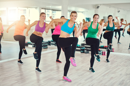synchronously: Group of fit young women doing exercise synchronously Stock Photo