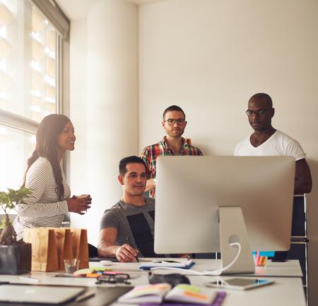 Groupe diversifié de jeunes entrepreneurs adultes noirs, hispaniques et caucasiens ensemble au bureau des petites entreprises avec une grande fenêtre lumineuse