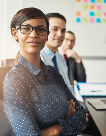 Confident smiling business woman wearing eyeglasses and white polka dotted shirt seated with folded arms beside male co-workers at work