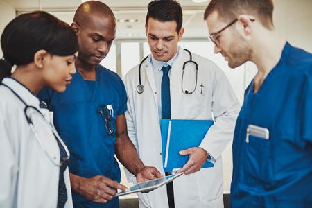 Team der multiracial Ärzte im Krankenhaus einen Patienten zu diskutieren, indem Ärzte Tablette