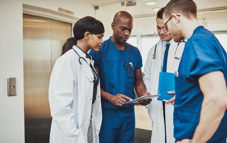Black chirurg geven van instructie aan medische team gemengde rassen met behulp van tablet