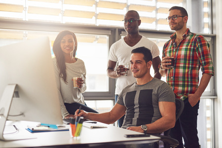 Four relaxed young diverse male and female small business workers with drinks in hand standing around computer in office