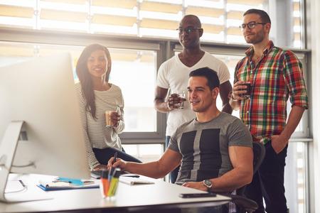 Vier entspannte junge vielfältigen männlichen und weiblichen kleinen Unternehmen Arbeiter mit Getränken in der Hand herumstehen Computer im Büro