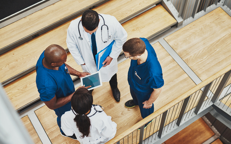 Multiracial medical team having a discussion as they stand grouped together around a tablet computer on a stair well, overhead view Stockfoto