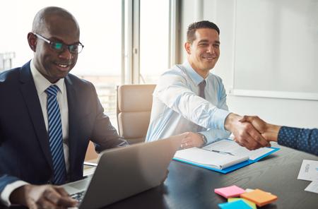 seated man: Hombre joven sonriente mujer de negocios hispanos y de darle la mano a través de una mesa en la oficina de vista por un gerente sonriente del afroamericano Foto de archivo
