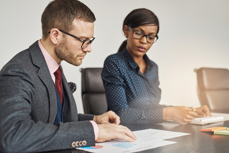 Businessman and women having a serious meeting sitting together reading a document or report with focus to a young man in glasses in the foreground