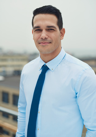 Young handsome Hispanic business man standing on a rooftop of an urban commercial building smiling at the camera