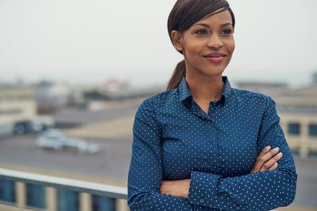 Überzeugte freundliche schwarze Business-Frau mit verschränkten Armen auf dem Dach eines städtischen Geschäftshaus stand lächelnd, als sie an der Seite der Kamera schaut