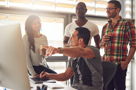 Man with stylus and tablet showing something on his computer to a group of three male and female casually dressed co-workers holding drinks
