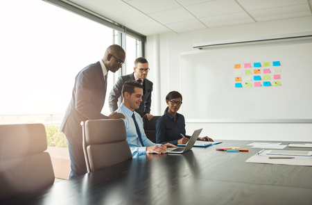 Group of four Black and white young business people at conference table looking at laptop with sticky note chart on board