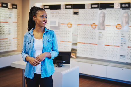 stood: Smiling female entrepreneur in her shop looking out happy Stock Photo