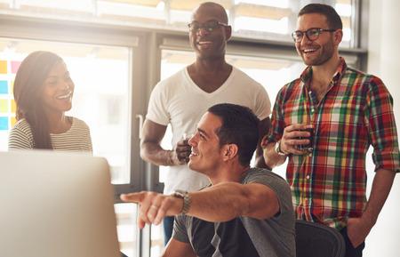 Knappe jonge volwassene iets op zijn computer tonen aan een groep van drie mannelijke en vrouwelijke terloops gekleed vrienden drankjes te houden
