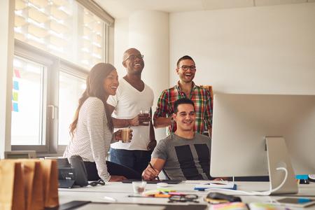 Lachen Frau und drei Männer Getränke rund um Computer mit Stift und Tablett auf Schreibtisch im Büro Beiläufig gekleideter halten