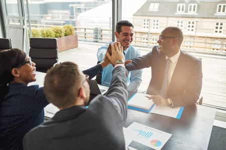 congratulations: El éxito Equipo de negocios multirracial sentados en una mesa en una oficina que anima urbana y felicitando entre sí después de un logro excepcional Foto de archivo