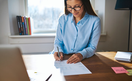 home business: Successful female entrepreneur or small business owner working at her desk at home in the office writing notes or sining a document with a smile, backlit by sun through a window