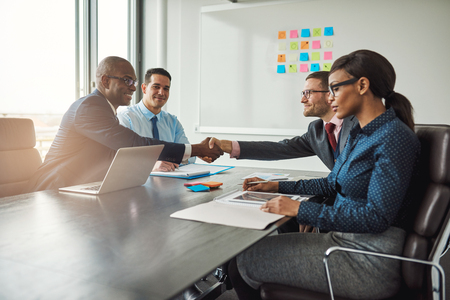 Duas jovens equipes de negócios multirraciais chegar a um acordo em negociações estendem-se através da mesa na sala de conferência para apertar as mãos