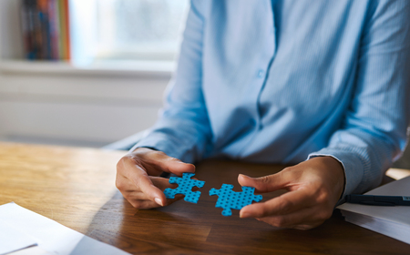 people problems: Cropped view close up of female hands at desk assembling two blue jigsaw puzzle pieces for concept about self employed people solving problems Stock Photo