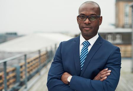 Zelfverzekerd zwarte zakenman in een stijlvolle pak staan met gevouwen armen op een dak van n kantoorgebouw te kijken naar de camera met een ernstige uitdrukking