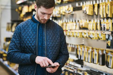 hardware: Hombre joven que controla un mensaje de texto en su teléfono móvil como hace la compra en una tienda de ferretería para los suministros de bricolaje