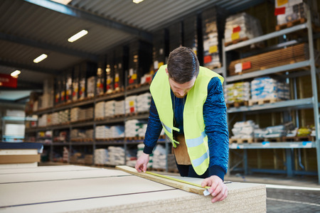Young handyman working in a building supplies or hardware warehouse checking lumber on a table