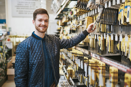 hobbyist: Smiling confident male customer in a hardware store standing smiling at the camera as he selects a product for DIY renovations off the rack Stock Photo