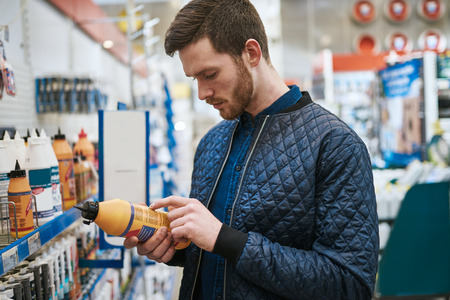 Aantrekkelijke jonge man die een product in een hardwarewinkel selecteert die het etiket op een fles met een uitgesproken uitdrukking leest