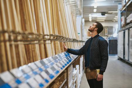 Carpenter het selecteren van hout in een ijzerhandel of magazijn permanente kijken lengte gesneden op een rek, zijaanzicht