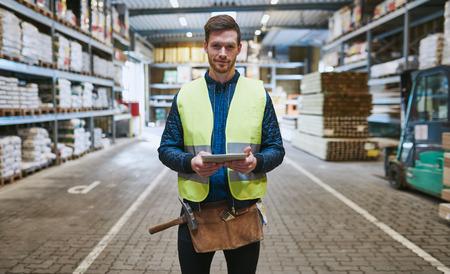 Jeune homme à tout faire ou constructeur debout dans le lecteur par le biais dans un entrepôt de matériel avec une tablette dans sa main regardant la caméra