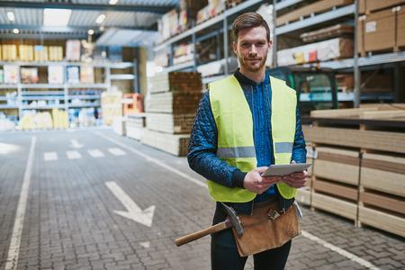 trabajadores: manitas joven guapo o supervisor del almacén se coloca entre los materiales de construcción con una tableta en la mano sonriendo a la cámara