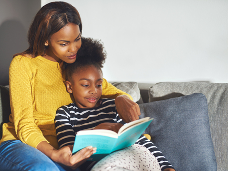 Mom teaching daughter to read in relaxed environment
