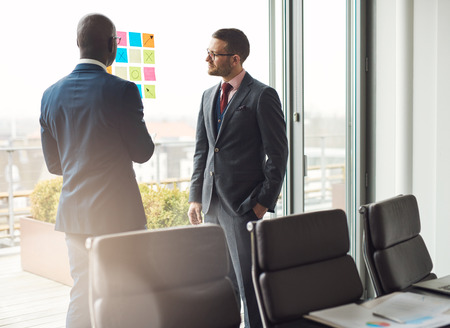 planned: Two business man in stylish suits standing having a discussion in the office looking at a colorful array of sticky memos on the window with ideas or a planned schedule