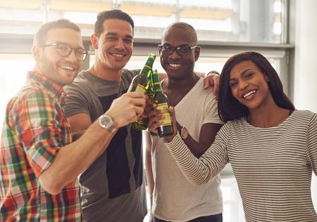녹색 유리 맥주 병을 도청 캐주얼 의상에서 4 명의 젊은 웃는 친구의 다양한 그룹 스톡 콘텐츠