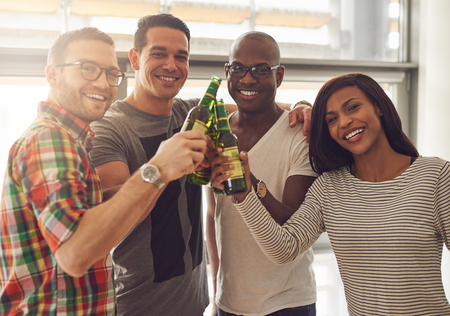Diverse group of four young smiling friends in casual outfits tapping green glass beer bottles